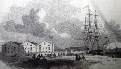 Etching of a ship docked next to warehouses.