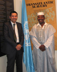 Two smiling men, one in a suit, the other in traditional African clothing, in front of display panels