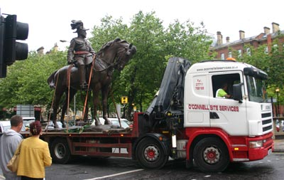 Monument of man on horse strapped to the back of a flat bed lorry, watched by pedestrians
