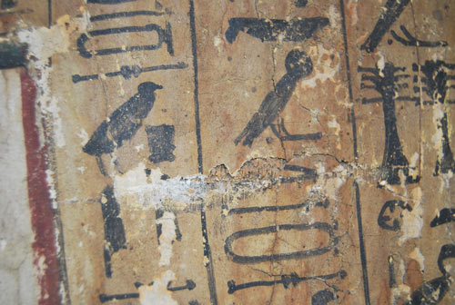 Close-up shot of the hieroglyphs: notice the flaking paint and areas of loss.