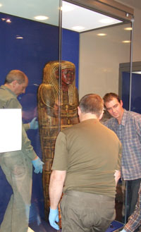 people installaing an Egyptian coffin in a display case
