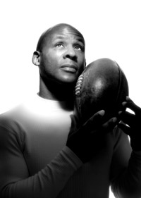 A portrait shot of man looking upwards and holding a rugby ball