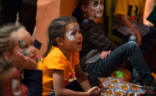 children with their faces painted, listening intently to an unseen storyteller