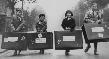 archive photo of 4 young children carrying suitcases