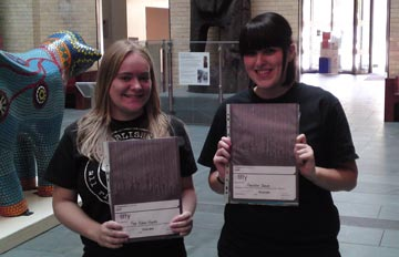 two young ladies holding certificates in the museum