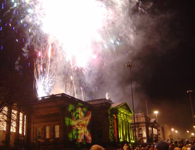 firewroks being launched from the roof of a neoclassical building at night