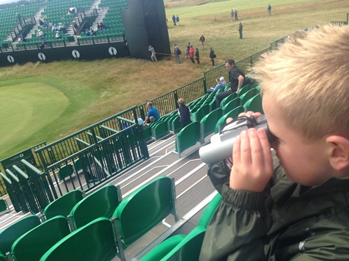 young child with binoculars looking at golf green