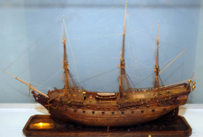 Colour photo of a wooden ship model. It has 3 large masts and a small boat on the deck.