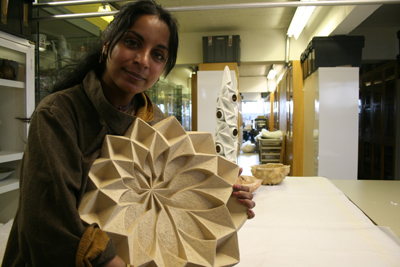 The artist holding an intricate geometric ceramic structure.