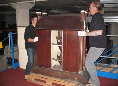 Two men lifting a large model house