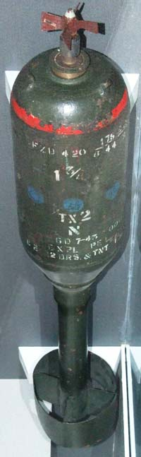 Photo of an old green bomb with fadded white lettering on the casing