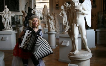 A woman playing an accordion in a gallery with classical statues and sculptures