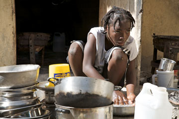 Young girl squatting to clean a large pile of pots and pans