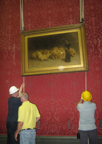two men in hard heights lifting a painting with ropes and pulleys