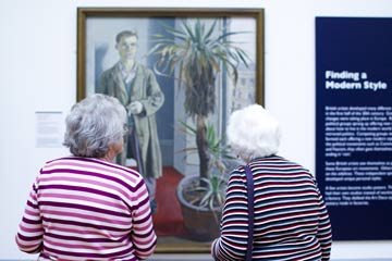 Two women look at a painting on the wall of a gallery