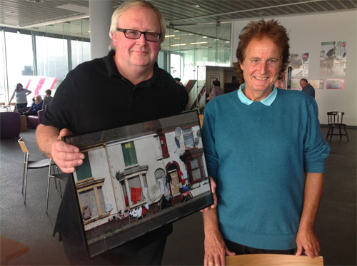 two men, one holding a framed photograph