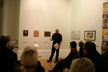 Artist talks to audience in gallery