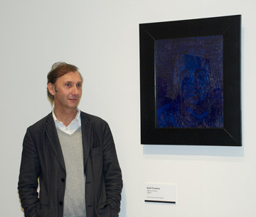 Man standing next to a blue portrait painting