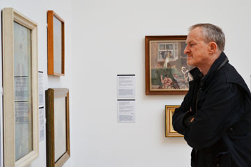John Kirby looking at paintings in the Walker