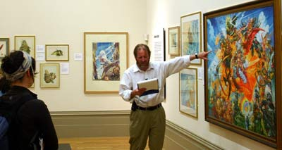 man pointing at a painting while reading from a clipboard