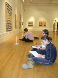 Two girls sitting on the floor of a gallery with drawing materials