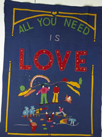 Blue blanket with 'All You Need is Love' and figures embroidered on it