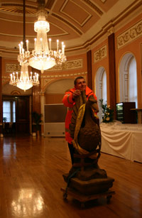 Man wheeling Liver Bird sculpture through a ballroom