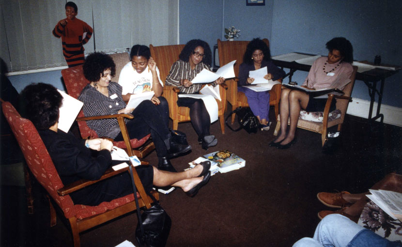 Women sat in a circle, looking at documents