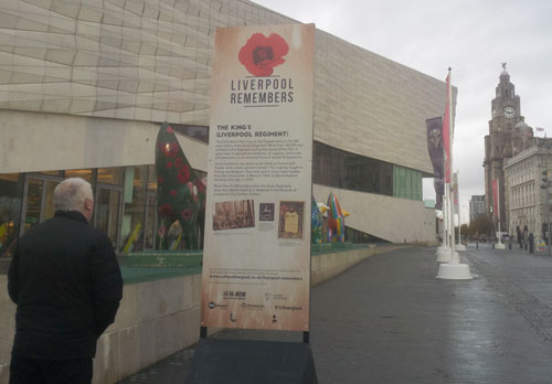 man looking at a large sign with a poppy logo and trail information