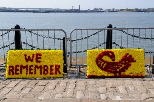 floral tributes on the dockside. Bright yellow and red wreaths with the words WE REMEMBER