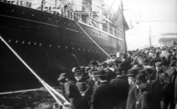 Black and white photo of crowds on a dockside beside a liner.