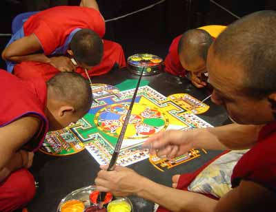 four men in red robes bending over a colourful pattern