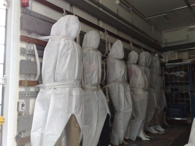 row of covered mannequins strapped inside a van in a standing position, with their shoes showing from under the sheet