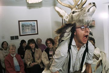 Man dressed in a deer skin, shouting in front of an audience