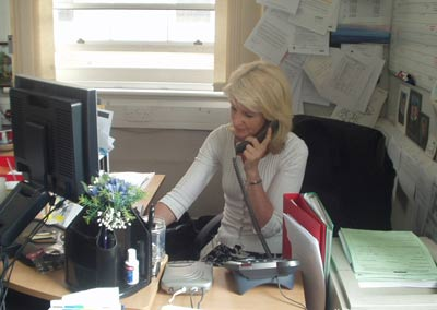 Photo of a blond woman sitting at a computer screen and speaking on a telephone