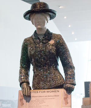 sculpture of woman holding a 'votes for women' sign