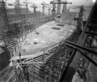 huge ship under construction, surrounded by cranes