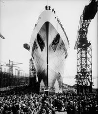 Black and white photo of the bow of a ship on a runway. There are crowds around.