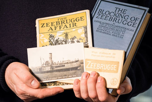 man holding old books about the First World War