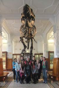group of volunteers standing in front of a Tyrannosaurus Rex in Manchester Museum