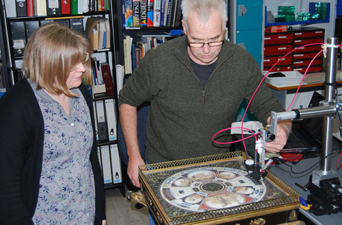 conservators using technical equipment to examine a decorative table