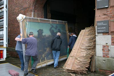 men carrying painting into museum