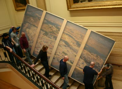 People carrying a large painting down a grand staircase