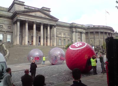 men rolling inflatable balls larger than they are in front of World Museum Liverpool