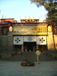 A pale brick built building with steps leading up the entrance. Its pagaoda style roof is decorated with gilt Tibetan Buddhist embelms