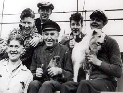 Sailors, a dog and a monkey pose for a photo