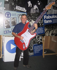 man holding a giant cut-out guitar