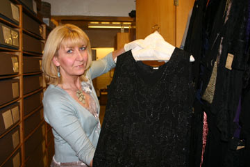 Curator holding a black sparkly dress