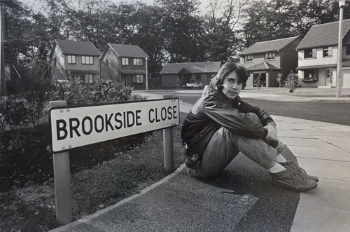 Phil Redmond sitting by a 'Brookside Close' street sign
