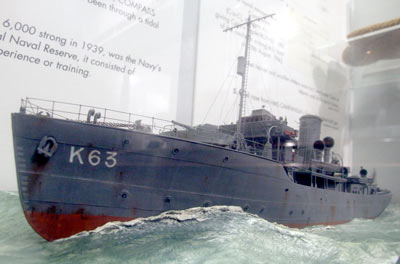 Photo of a model of a grey ship at sea. It has a red hull and the number K63 on its side
